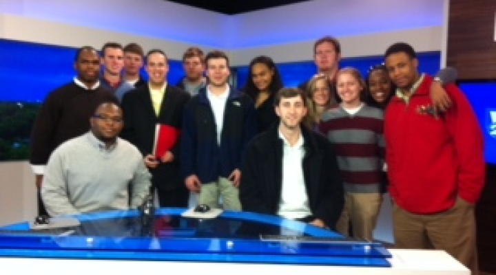 Students behind TV anchor DEsk