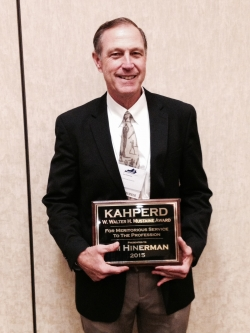 EKU faculty member Jim Hinerman receiving the Mustaine Award from KAHPERD